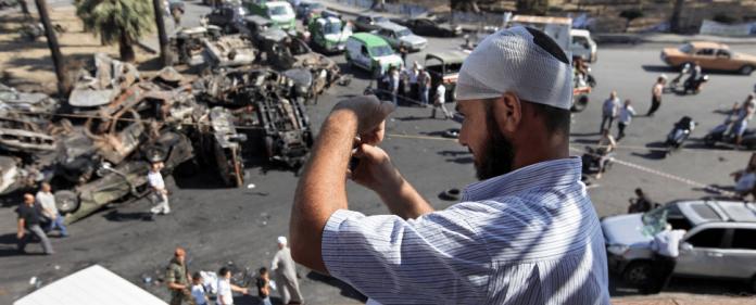 Ein verletzter Mann mit seinem Mobilgerät in Tripoli. Kurz zuvor detonierten zwei Bomben. Dutzende starben, Hunderte wurden verletzt.