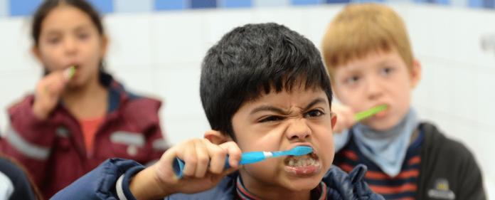 Kinder putzen ihre Zähne in einer Schule. dpa