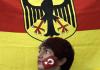 Vor der deutschen Flagge ein Mann, der eine Gesichtsbemalung hat - zaman