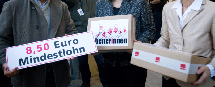 Der verdi-Vorsitzende Frank Bsirske (l) übergibt der amtierenden Bundesministerin für Arbeit und Soziales, Ursula von der Leyen (CDU, r), und die SPD-Generalsekretärin Andrea Nahles (M) am 16.11.2013 in Berlin eine Unterschriftensammlung für einen branchenübergreifenden flächendeckenden Mindestlohn von 8,50 Euro - dpa