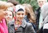 Merkel begrüßt muslimische Schülerinnen.