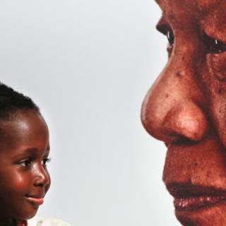 Ein kleines Mädchen lächelt vor dem Portrait von Nelson Mandela - dpa