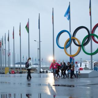 Olympia-Helfer nehmen in Sotschi ein Foto unter den Olympia-Ringen auf.