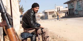 Ein Mann sitzt neben einer Waffe - Syrien - reuters