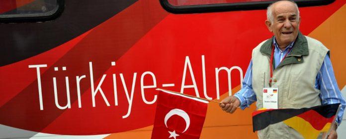 Ein älterer Mann, mit der türkischen Flagge und der deutschen Flagge vor dem
