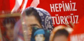 """Eine Türkin hält ein Schild hoch, worauf """"Wir sind alle Türken"""" zu lesen ist."""