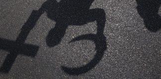 Das Bild zeigt den Schatten eines Mannes, der ein Kreuz und einen Halbmond in der Hand hält.