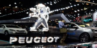 The exhibition area of Peugeot reflects in a car during the second press day of the Paris Motor Show (Mondial de l'Automobile) in Paris, France, 3 October 2014.