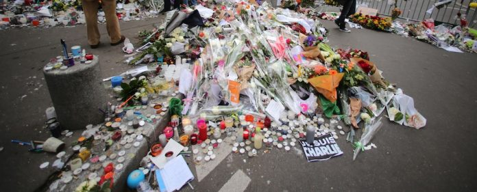 Menschen haben Blumen, Kerzen und Notizen zum Gedenken an die Opfer des Terrors in Paris niedergelegt. (dpa)
