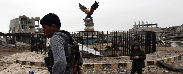 Das Zentrum von Kobane ist verwüstet. Ein junger Kämpfer der YPG läuft auf dem Azadiyya-Platz.