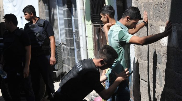 Ein türkischer Polizist durchsucht einen jungen Mann in einer Gasse.