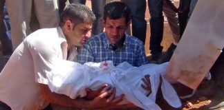 Zwei Männer halten den in ein weißes Leichentuch gehüllten Aylan Kurdi und heben ihn in sein Grab.