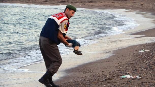 Ein türkischer Polizist trägt den Leichnam von Aylan Kurdi vom Strand.