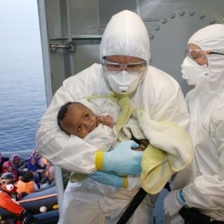 Marinesoldaten der Bundeswehr versorgen ein Baby, das von einem Fl+chtlingsboot gerettet wurde